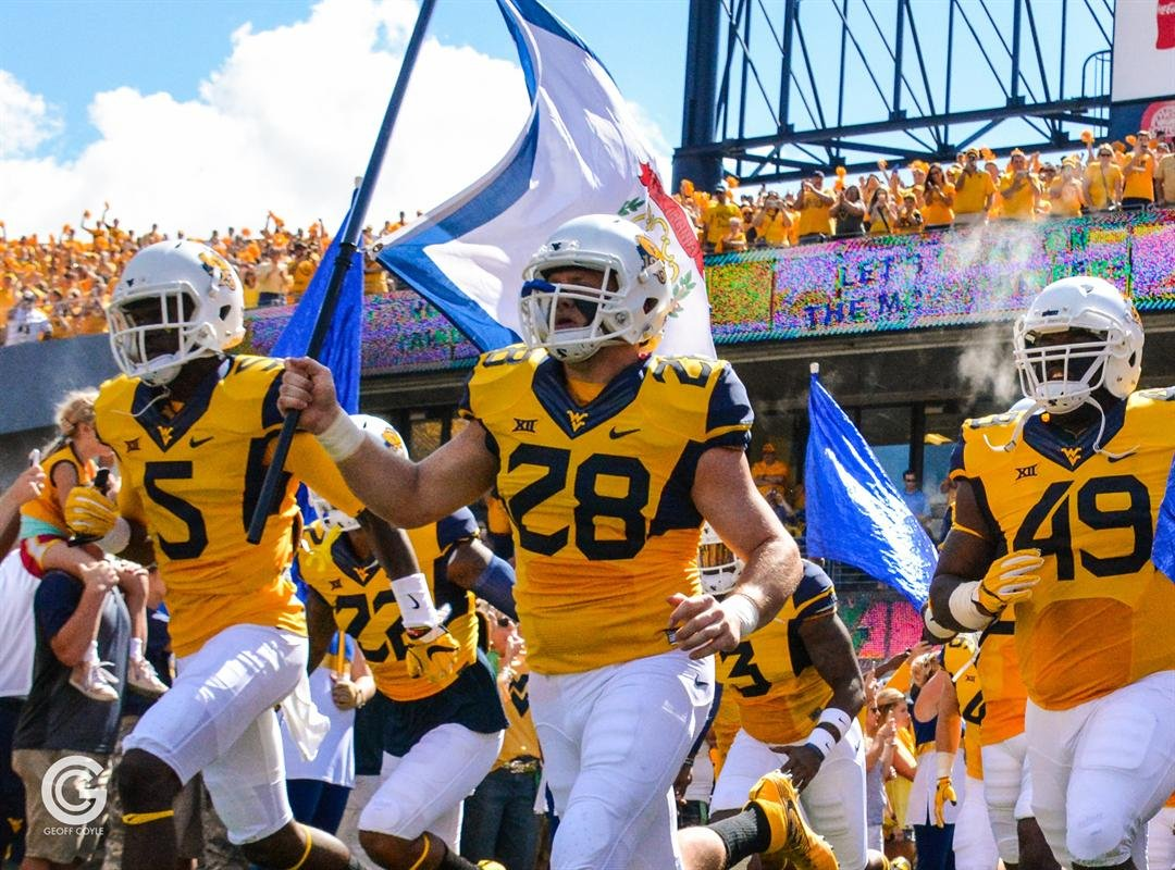 Buffalo Creek native Elijah Wellman carries the West Virginia state flag onto the field for the season opener against Missouri. (PHOTO: Emily Coyle)