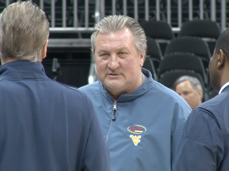 Bob Huggins talks with his assistants on the court at the Big 12 Tournament.