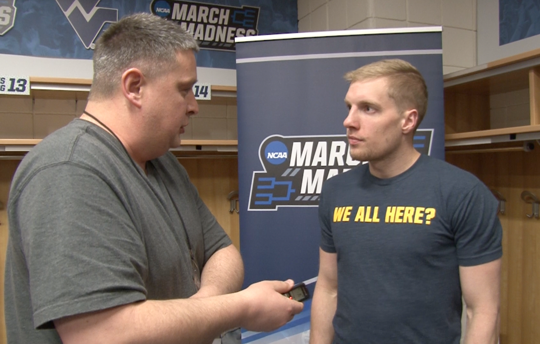 """WVU senior James Long sports a """"We all here?"""" t-shirt during an interview at the NCAA Tournament in Buffalo."""