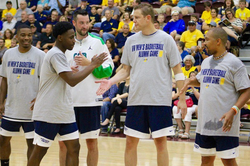 Juwan Staten high-fives his teammates as he takes the court during the WV Men's Basketball Alumni Game (PHOTO: Anjelica Trinone).