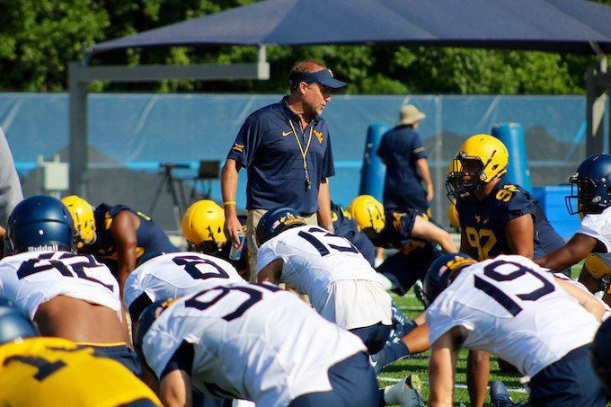 Coach Holgorsen talks with the players during warm-ups at fall camp. (PHOTO: Anjelica Trinone)