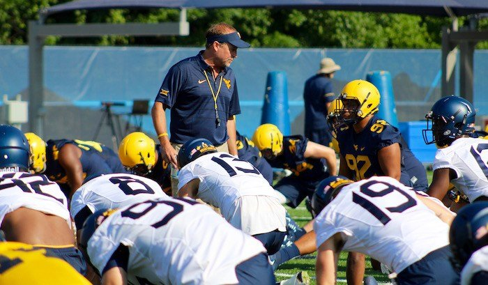 Coach Holgorsen talks to the players during stretches at fall camp. (PHOTO: Anjelica Trinone)