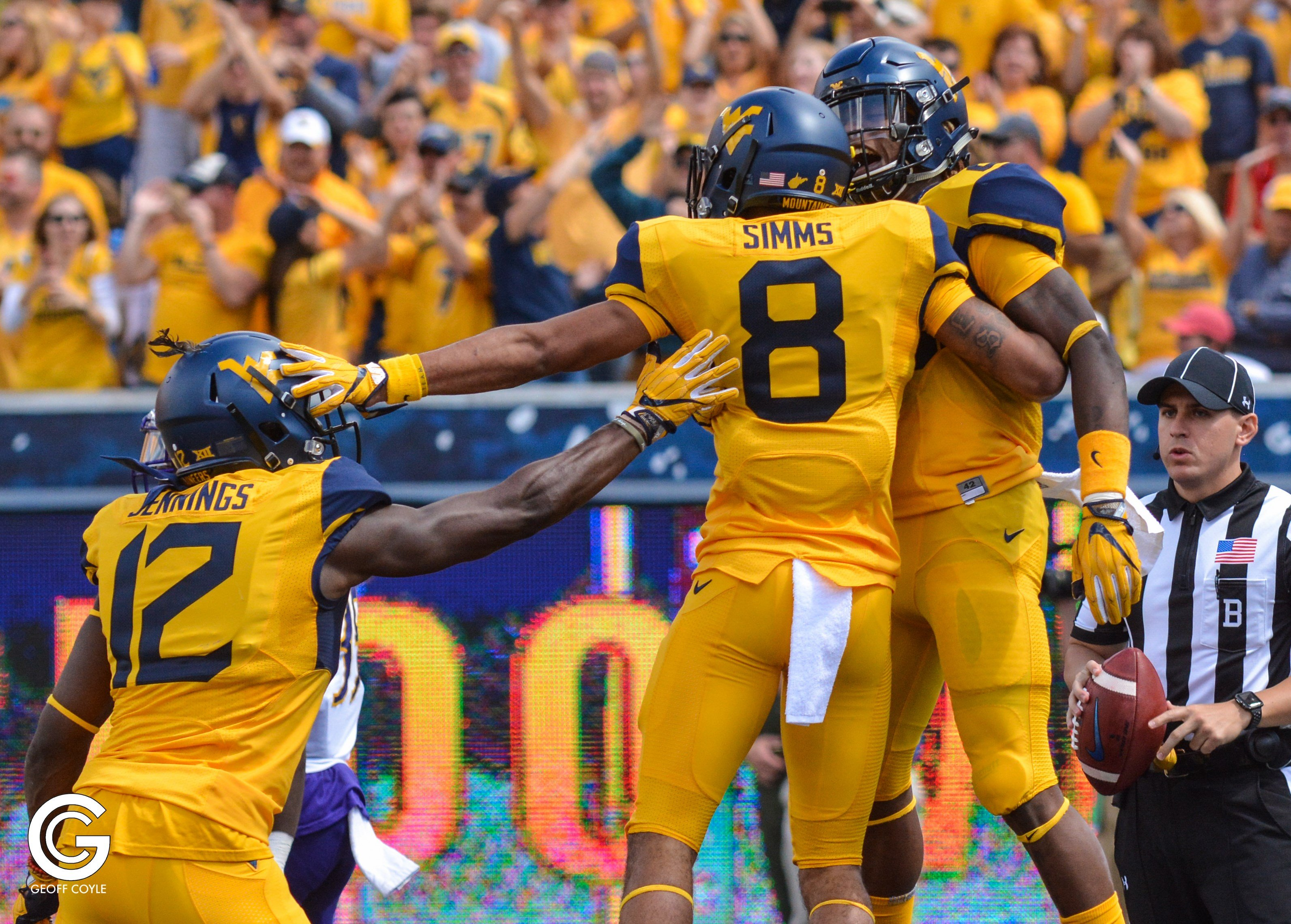 Gary Jennings (12), Marcus Simms (8) and Justin Crawford celebrate a WVU touchdown. (PHOTO: Geoff Coyle)